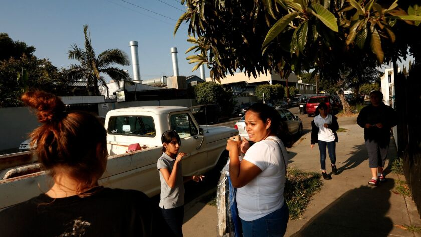 Alicia Hernandez, 29, center, lives across the street from the Bowman Plating Company, one of many metal finishing and chemical processing companies operating in Compton, on June 1.