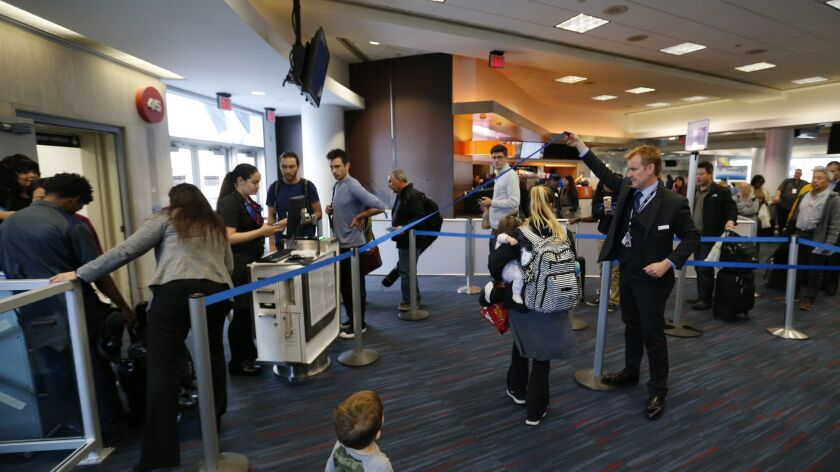 LOS ANGELES, CA -- TUESDAY, DEC. 12, 2016: Passengers line up to board American Airlines 2381 fligh