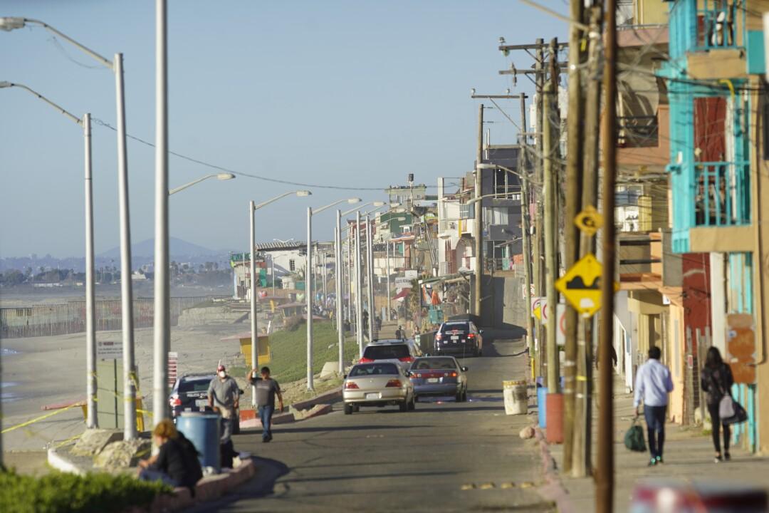 Pedestrians walk in a neighborhood alongside a beach.