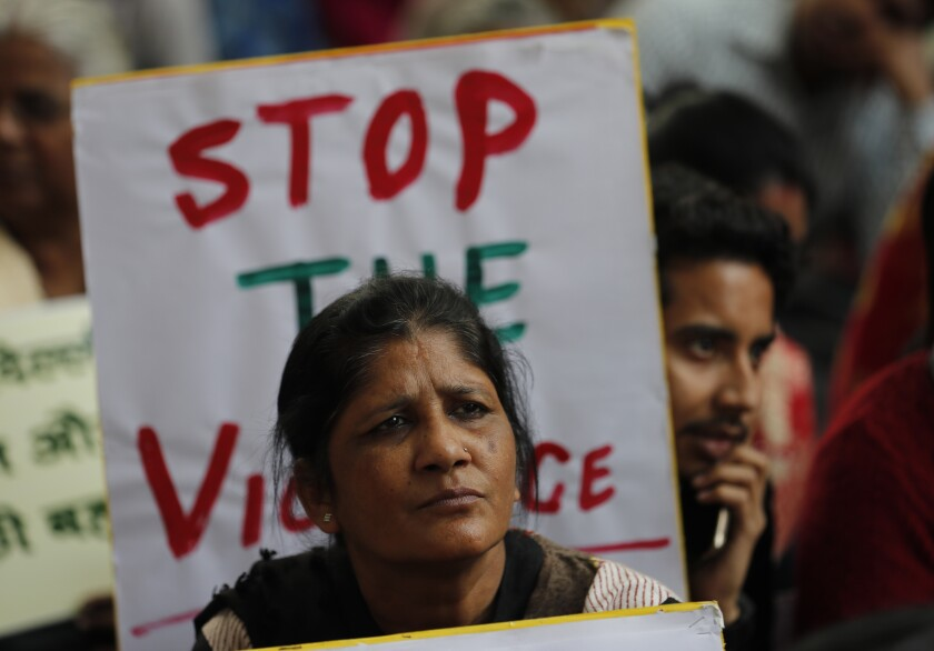 Activists hold banners calling for peace following violence Feb. 26 in New Delhi.