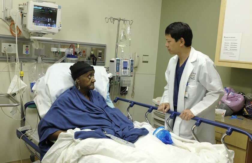 """Dr. Ted Chan speaks with patient Rosalind Stroud, 74, about the abdominal pain that brought her to Thornton Hospital's emergency department this week. Chan and other UC San Diego doctors, are working with nonprofit West Health on a new """"Acute Care at Home"""" program that seeks to deliver some services that usually require admission at patients' residences."""