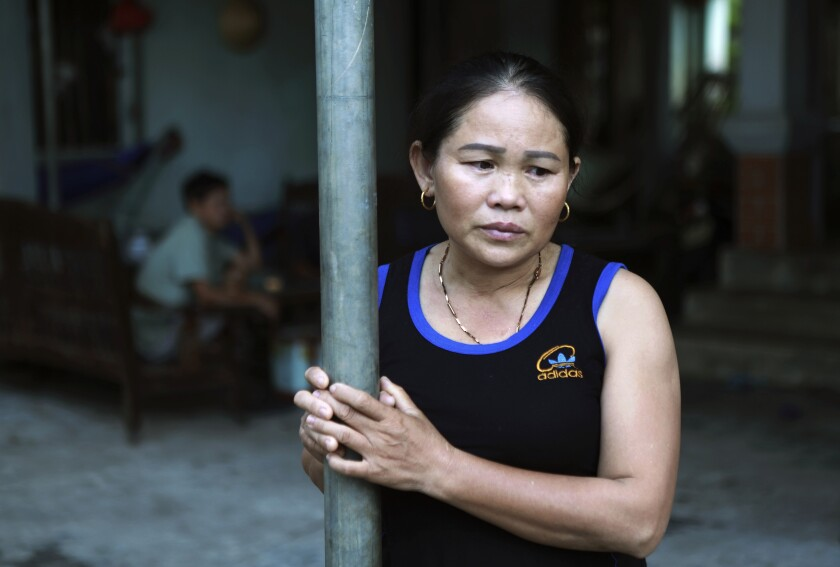 In this Oct. 28, 2019, photo, Hoang Thi Ai, mother of Hoang Van Tiep, who is feared to be among the England truck dead, stares off at home in Dien Thinh village, Nghe An province, Vietnam. For many Vietnamese, a job in a Western European country is seen as a path to prosperity worth breaking the law for. But the risks of doing so are high and the consequences can be deadly, as the discovery of 39 bodies in a truck in England last week proved. (AP Photo/Hau Dinh)