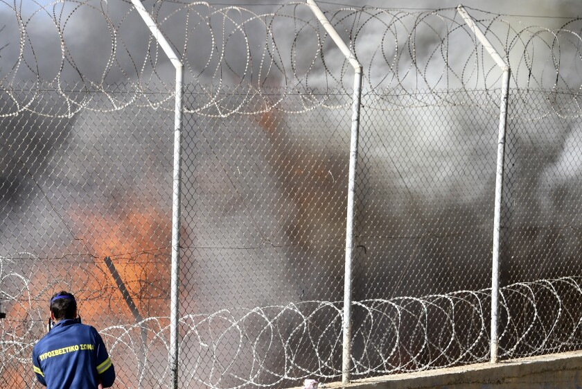 A firefighter tries to extinguish a fire inside a refugee camp on the eastern Aegean island of Samos, Greece, Wednesday, Nov. 11, 2020. Dozens of accommodations were destroyed by the fire that broke out on Wednesday morning. (AP Photo/Michael Svarnias)