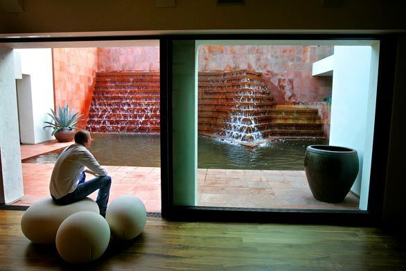 When Tim Campbell was hired to redesign a Los Angeles property with a fountain credited to Mexican master architect Luis Barragán, he faced not only the pressure of building next to a potential piece of architectural history, but also the task of sorting out the jumbled house around it. Here, Campbell sits in an expansive entertaining area with sliding glass doors open to the pool and fountain.