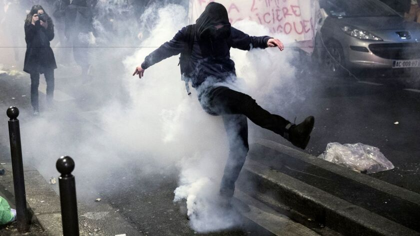 A protester in Paris kicks back a gas canister during a demonstration against police violence Feb. 15.