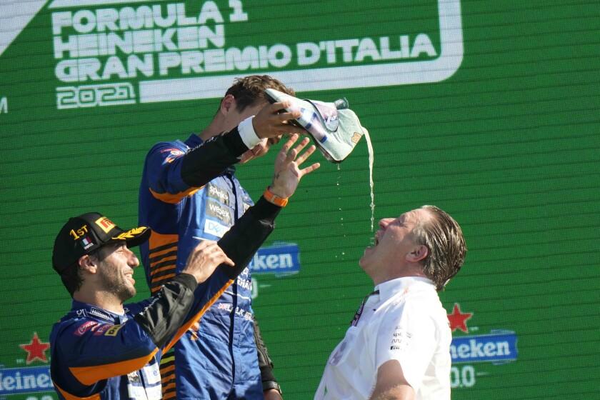 Zak Brown bebe champagne que le sirven Daniel Ricciardo