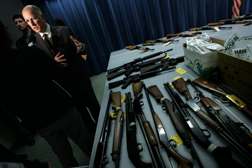 Spearking at Dec. 10, 2007, news conference in Los Angeles, Gov. Jerry Brown, then attorney general, shows guns seized from criminals during a law enforcement operation.