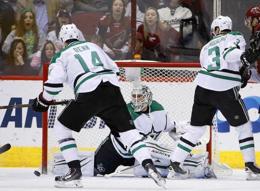Dallas Stars goalie Antti Niemi, middle, of Finland, slides over to make a save on a shot by the Arizona Coyotes as Stars' Jamie Benn (14) and John Klingberg (3), of Sweden, watch during the first period of an NHL hockey game Thursday, Feb. 18, 2016, in Glendale, Ariz. (AP Photo/Ross D. Franklin)