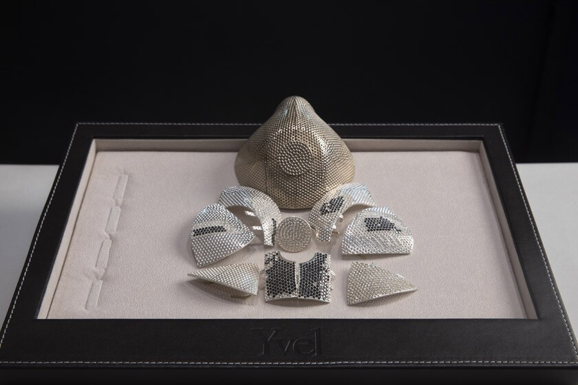 Several pieces of an 18-karat white gold mask are displayed in front of a model of the face covering.