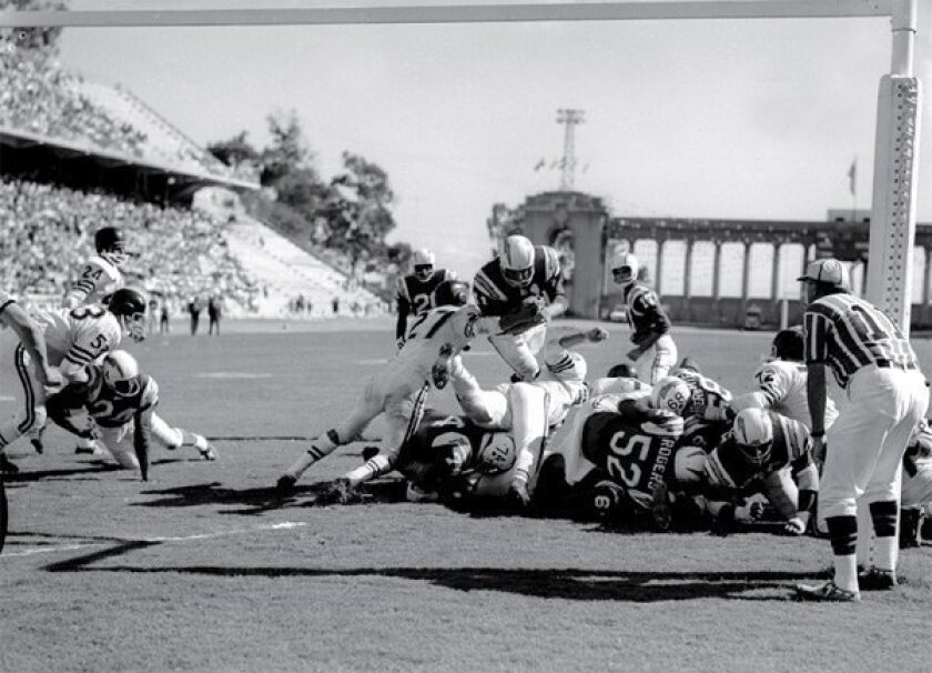 Chargers RB Charlie Flowers runs over the Raiders to score in a 1961 game at Balboa Stadium.  (San Diego Historical Society / Union-Tribune)