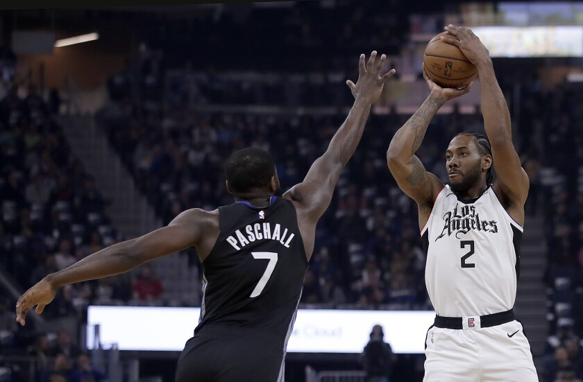 Kawhi Leonard puts up a shot in front of Golden State's Eric Paschall during the first half of a game March 10 at Chase Center.