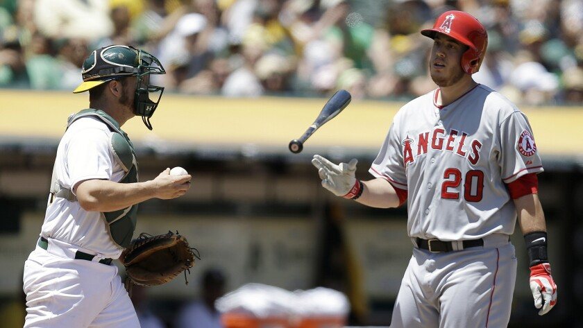 Angels first baseman C.J. Cron, right, reacts to striking out in front of Oakland Athletics catcher Sonny Gray during the second inning of the Angels' 6-3 loss Sunday.