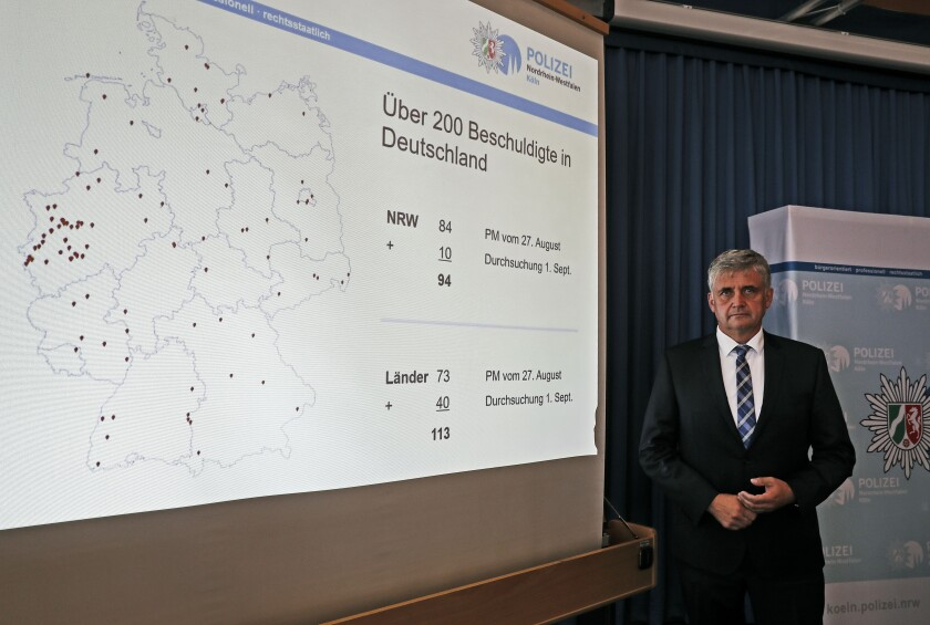 Michael Esser, head of the investigation group, stands beside a map of Germany at a press conference at the police department in Cologne, Germany, about nationwide child pornography raids, Wednesday, Sept. 2, 2020. Special police units, coordinated by the Cologne Prosecutor's Office, have raided 60 places across Germany yesterday, linked to an ongoing investigation that started last year in the city of Bergisch Gladbach. (AP Photo/Martin Meissner)