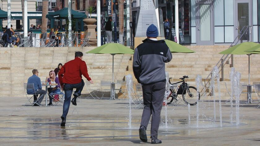 Steve Zimmers runs safely through the newly installed Horton Plaza park interactive  water feature. At night the lighting and water effects will be synched to music.