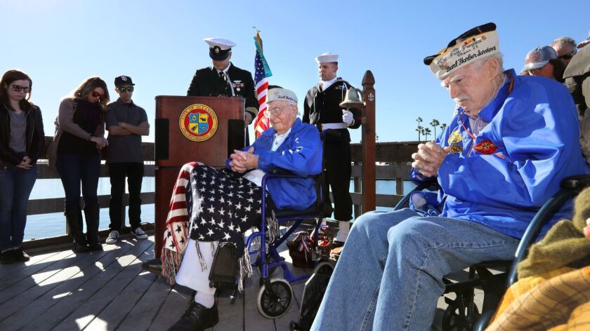 At the Pearl Harbor Memorial event at Oceanside Harbor this morning Pearl Harbor survivors John Quier, 98, left, and Joe Walsh, 99, right, listen as a bell is rung in memory of people killed in the attack. At the podium presiding over the event is Navy Se