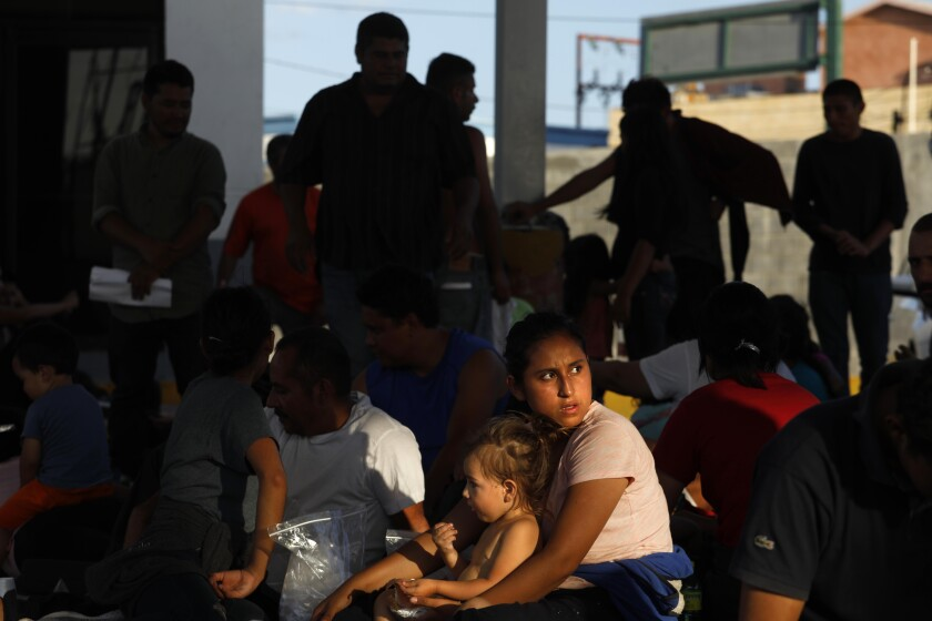 Asylum seekers wait in the parking lot of an immigration agency in Nuevo Laredo, Mexico