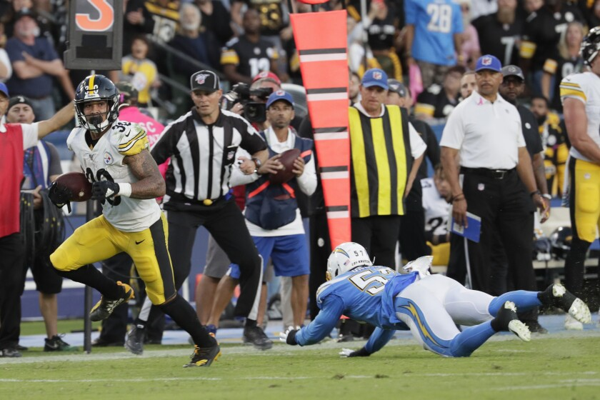 Pittsburgh Steelers running back James Conner, left, sprints past Chargers outside linebacker Jatavis Brown for a touchdown during the second quarter of the Chargers' 24-17 loss Sunday.