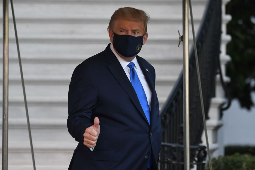 President Trump wears a mask and gives a thumbs-up