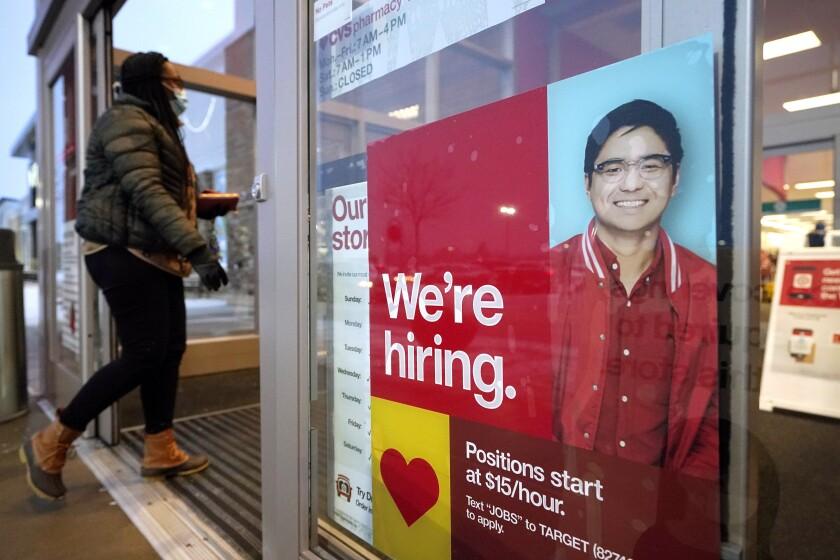 passer-by walks past an employment hiring sign