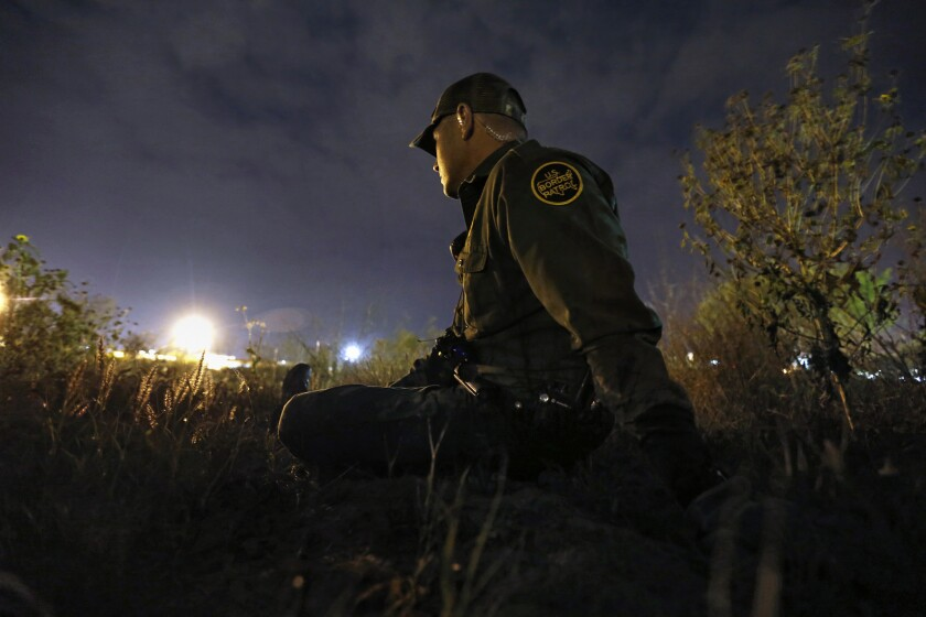 U.S. Border Patrol Agent Robert Trevino stays low as he waits for migrants to cross the Rio Grande in Roma, Texas.