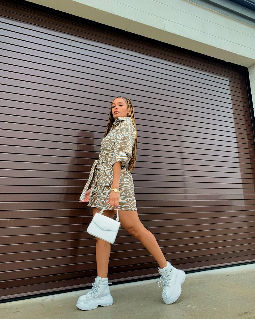 Lynette Adkins, holding a handbag and posing.