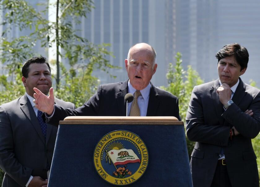 El gobernador de California Jerry Brown, centro, rodeado por el presidente del Senado Kevin de León, demócrata por Los Angeles, derecha, y el asambleista Eduardo García, demócrata por Coachella, izquierda, habla durante una conferencia de prensa antes de promulgar una ley de cambio climatico, el jueves 8 de septiembre del 2016 en Los Angeles. Brown extendió el jueves la ley de cambio climático más ambiciosa del país por otros 10 años, a la vez que el estado establece una nueva meta para reducir polución de carbono. (AP Foto/Richard Vogel)