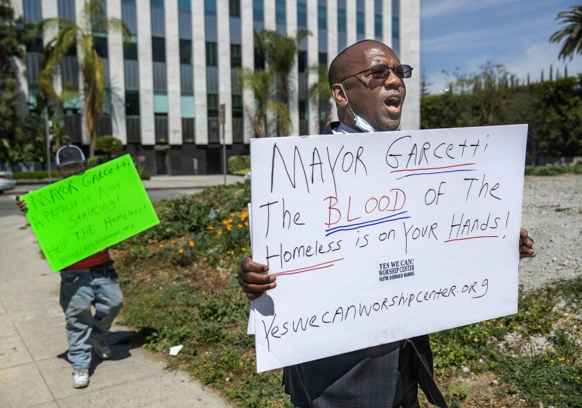 Miguel Rios, left, who is homeless, and Pastor Sherman Manning carry protest signs along Wilshire Boulevard in L.A.