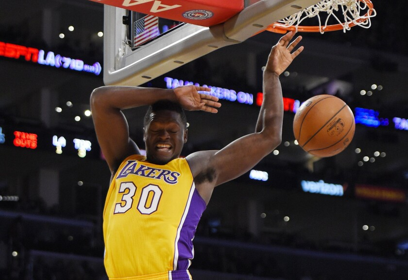 Lakers forward Julius Randle dunks during the second half of a game against the Raptors.