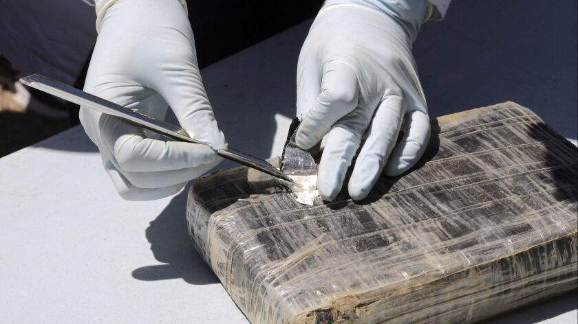 A technician cuts open a package of cocaine prior to its destruction in Tegucigalpa, Honduras, Frida