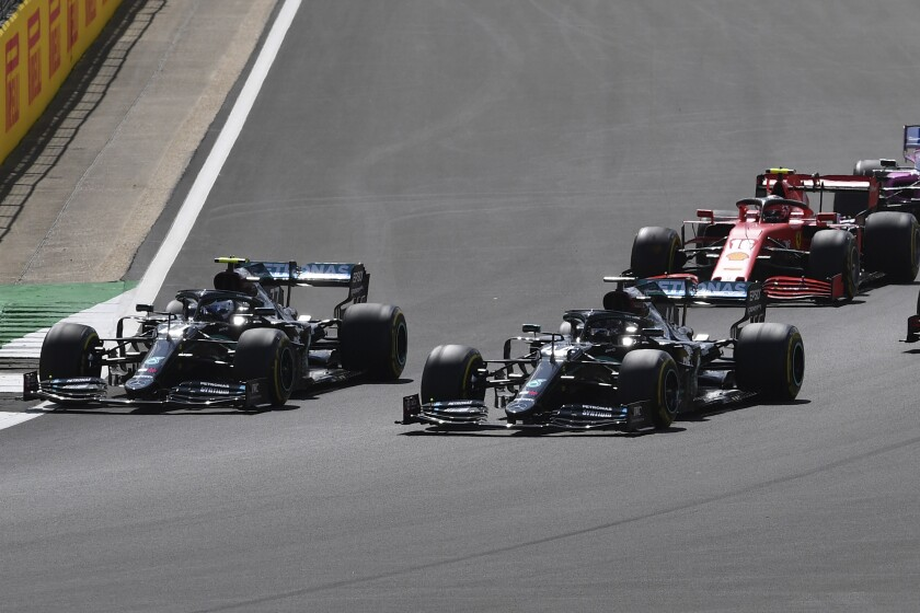 Mercedes driver Valtteri Bottas of Finland, left and Mercedes driver Lewis Hamilton of Britain steer their cars during the British Formula One Grand Prix at the Silverstone racetrack, Silverstone, England, Sunday, Aug. 2, 2020. (Ben Stansall/Pool via AP)