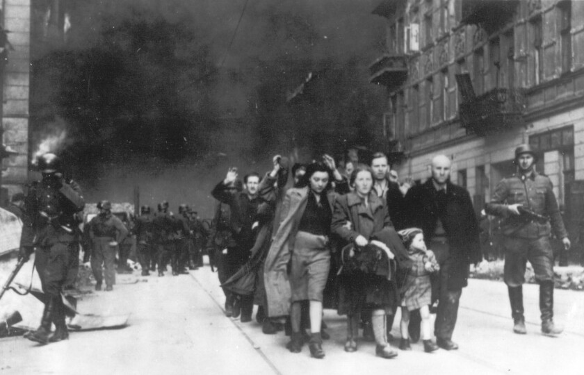 FILE - In this 1943 photo, a group of Polish Jews are led away for deportation by German SS soldiers, during the destruction of the Warsaw Ghetto by German troops after an uprising in the Jewish quarter. Two Polish historians are facing a libel trial for a scholarly examination of Polish behavior during World War II, a case whose outcome is expected to determine the fate of independent Holocaust research under Poland's nationalist government. A verdict is expected Feb. 9. (AP Photo, B/W File)