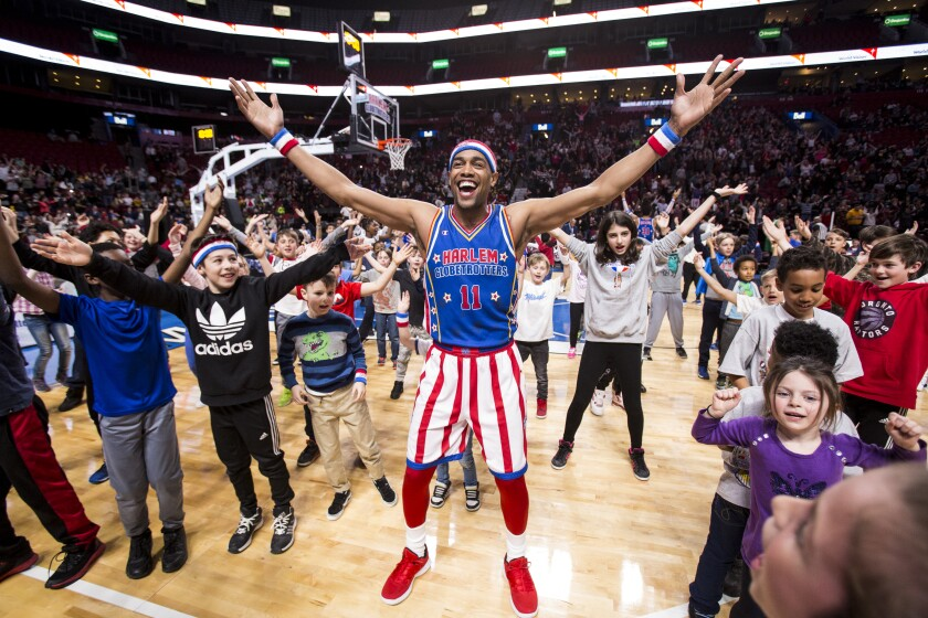 Cheese Chisholm of the Harlem Globetrotters interacts with young fans on the court.