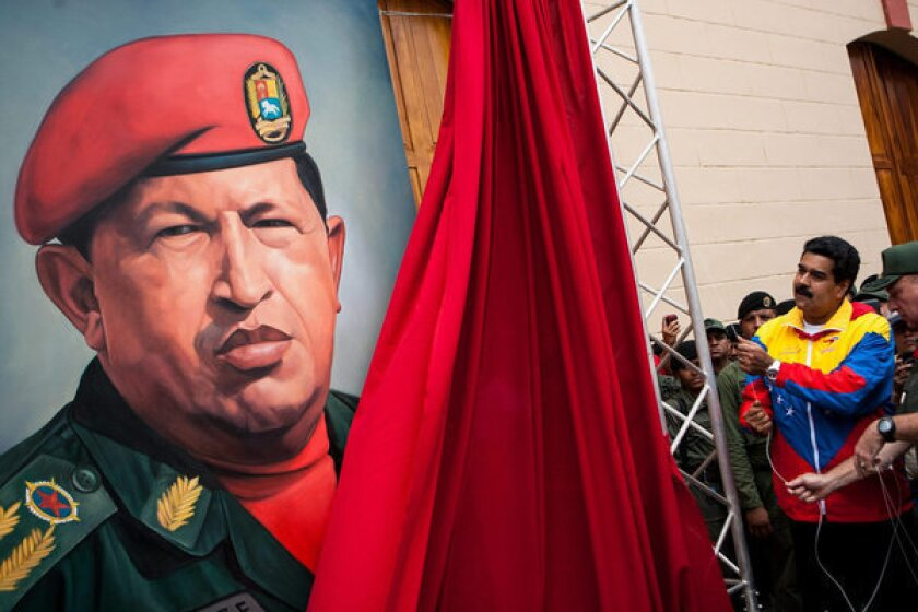 Venezuelan Vice President Nicolas Maduro, right, unveils a portrait of President Hugo Chavez, the fiery populist who declared a socialist revolution in Venezuela, crusaded against U.S. influence and championed a leftist revival across Latin America. Chavez died Tuesday at the age 58 after a nearly two-year bout with cancer.