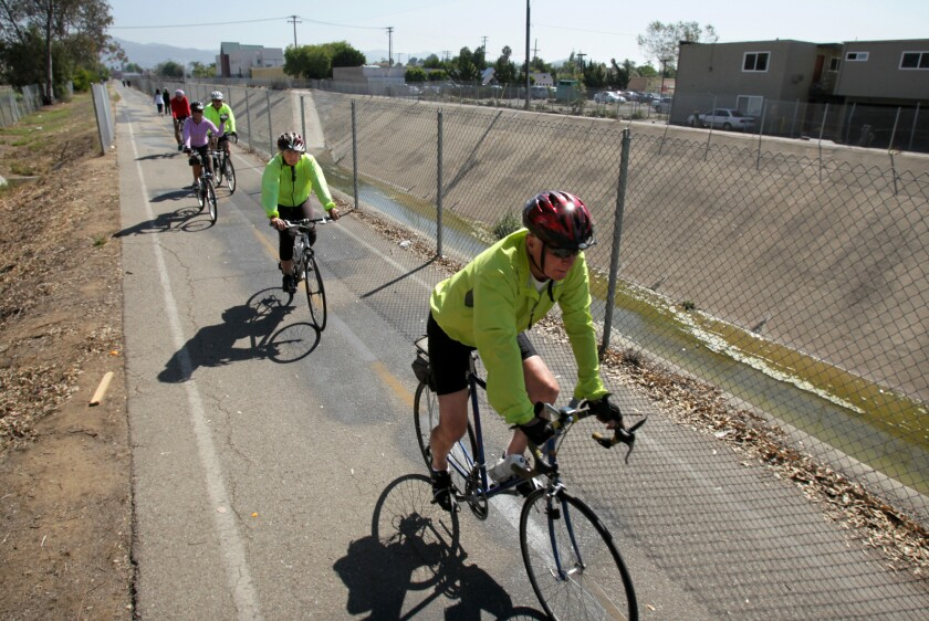 In this 2012 photo, bicyclists ride by a channelized section of Escondido Creek. The Escondido Creek Conservancy is launching plans to restore the creek to its natural state.