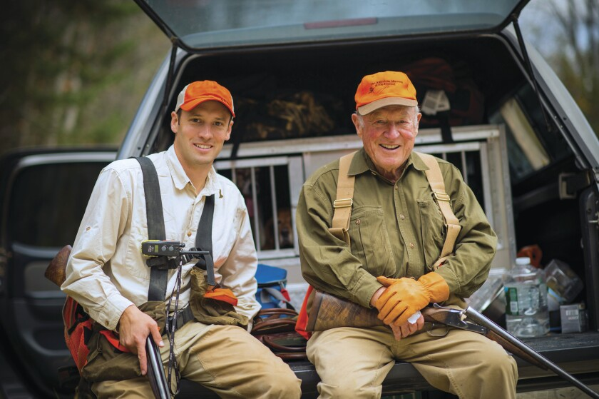 In this undated photo provided by Orvis, Simon Perkins, left, sits with his grandfather Leigh Perkins. Leigh Perkins, who transformed the Vermont-based Orvis company from a niche fly-fishing supply company into a global retailer of outdoor supplies, apparel and protector of the environment has died. He was 93. Leigh Perkins died May 7 in Monticello, Florida. Simon Perkins is now the company president, the third generation of his family to lead the company. (Brian Grossenbacher/Courtesy of Orvis via AP)