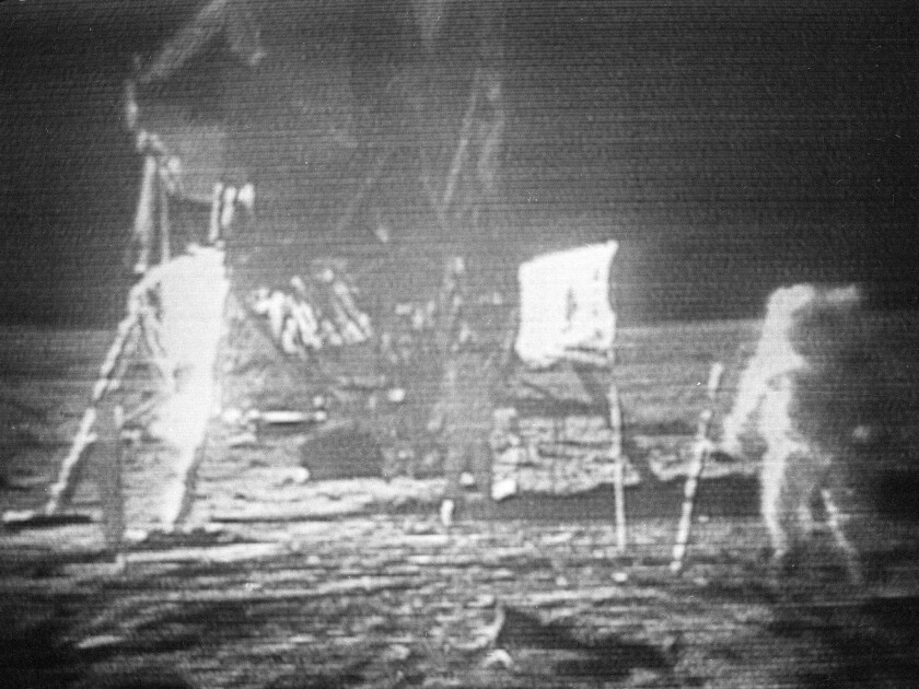 "In this July 20, 1969, image made from television, Apollo 11 astronaut Neil Armstrong, right, trudges across the surface of the moon. Edwin E. ""Buzz"" Aldrin is seen closer to the craft."
