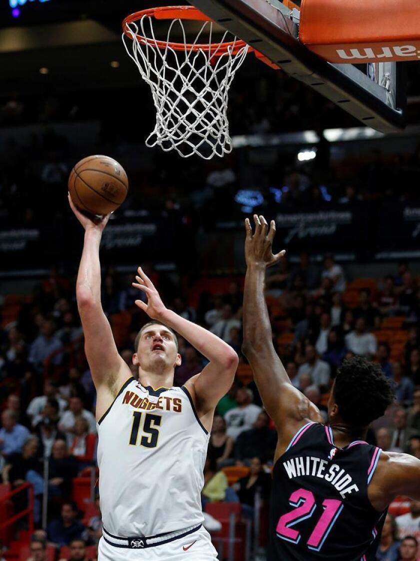 Nikola Jokic (i) de Denver Nuggets en acción ante Hassan Whiteside (d), durante un juego de la NBA entre Denver Nuggets y Miami Heat. EFE
