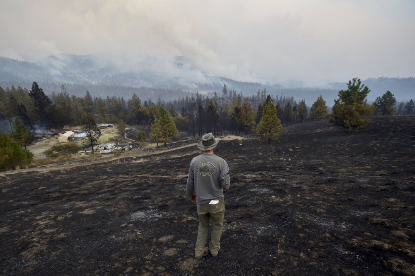 Lorne Brunson stands on a hill overlooking the remains of his homestead in Fruitland, Wash.
