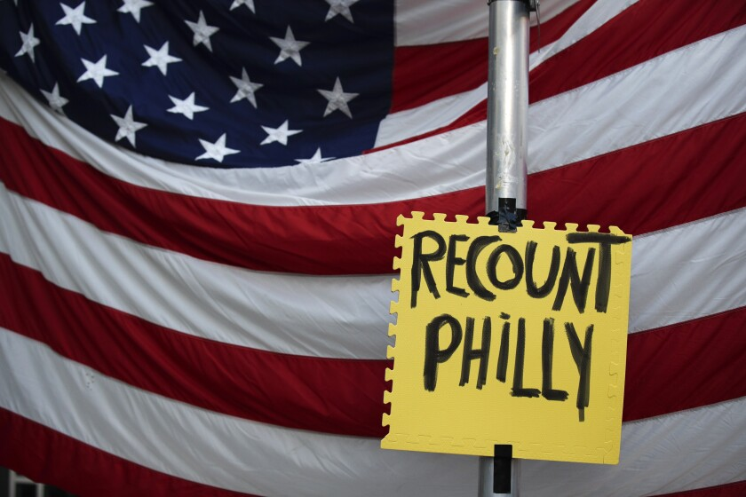 A sign hangs in front of an American flag, as a handful of supporters of President Donald Trump continue to protest outside the Pennsylvania Convention Center, in Philadelphia, Tuesday, Nov. 10, 2020. (AP Photo/Rebecca Blackwell)