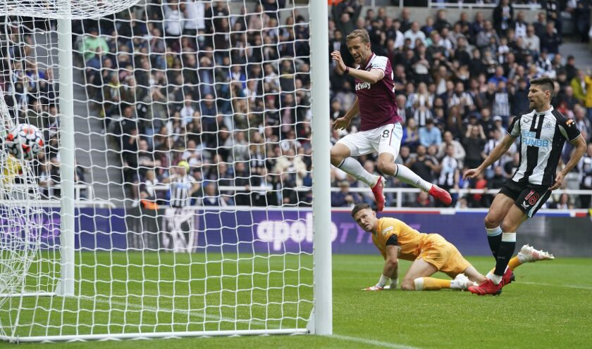 West Ham United's Tomas Soucek, in air, scores his side's third goal of the game from a penalty rebound, during the English Premier League soccer match between Newcastle United and West Ham United, at St. James' Park, in Newcastle, England, Sunday, Aug. 15, 2021. (Owen Humphreys/PA via AP)
