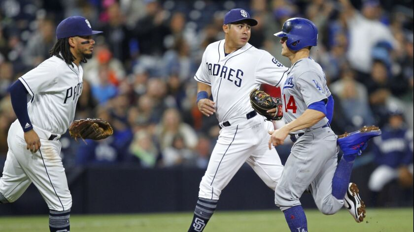 Enrique Hernandez of the Los Angeles Dodgers heads for third base as Padres shortstop Freddy Galvis, left, and shortstop Christian Villanueva wait for a throw in the third inning Monday at Petco Park.