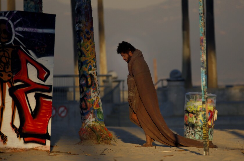 VENICE, CA DECEMBER 6, 2017: At dawn, a homeless man walks around Venice Beach wearing a blanket N
