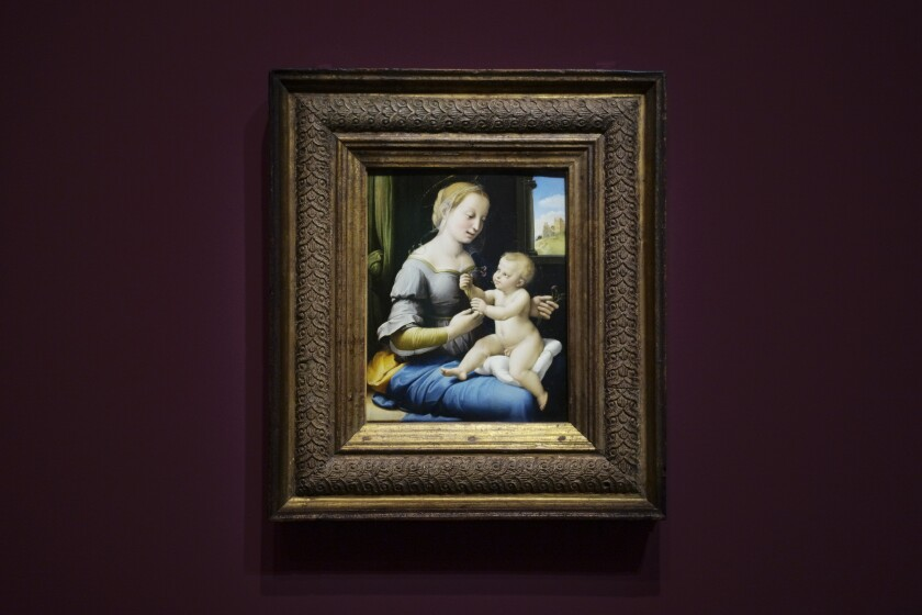 The painting 'Madonna of the Pinks' of Renaissance artist Raphael from London's National Gallery is on display at an exhibition at the Gemaeldegalerie in Berlin, Wednesday, Germany in 2019. Berlin is opening the first of several Raphael exhibitions as the art world celebrates the 500th anniversary of his death in 2020. The show is dedicated to five famous Madonna paintings by the renowned Renaissance master that belong to Berlin's Gemaeldegalerie collections and another masterpiece of the Virgin Mary that is on loan from the National Gallery in London.