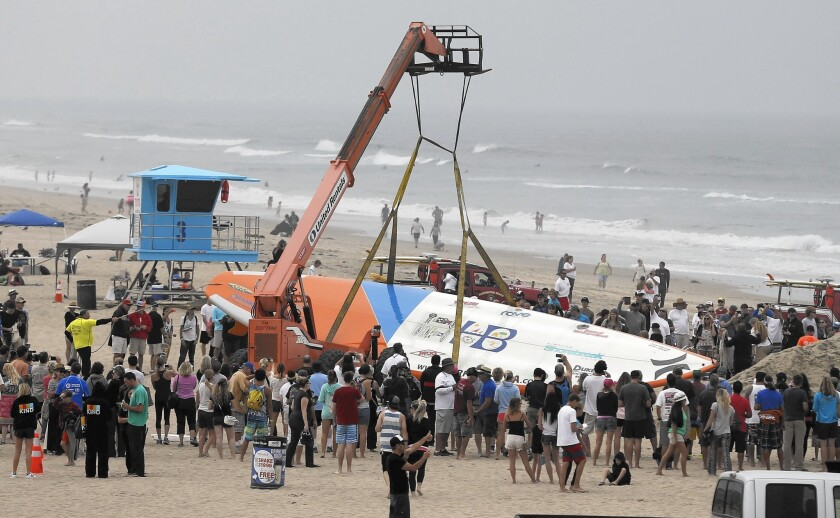Crowds gather as a crane carries a 42 1/4-foot surfboard to the water and to watch 66 surfers break the World Guinness Record for most people on a surfboard in Huntington Beach.