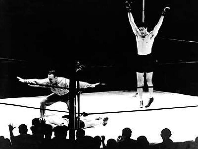 Max Schmeling raises his hands in victory after referee Arthur Donovan counts out Joe Louis on June 19, 1936.