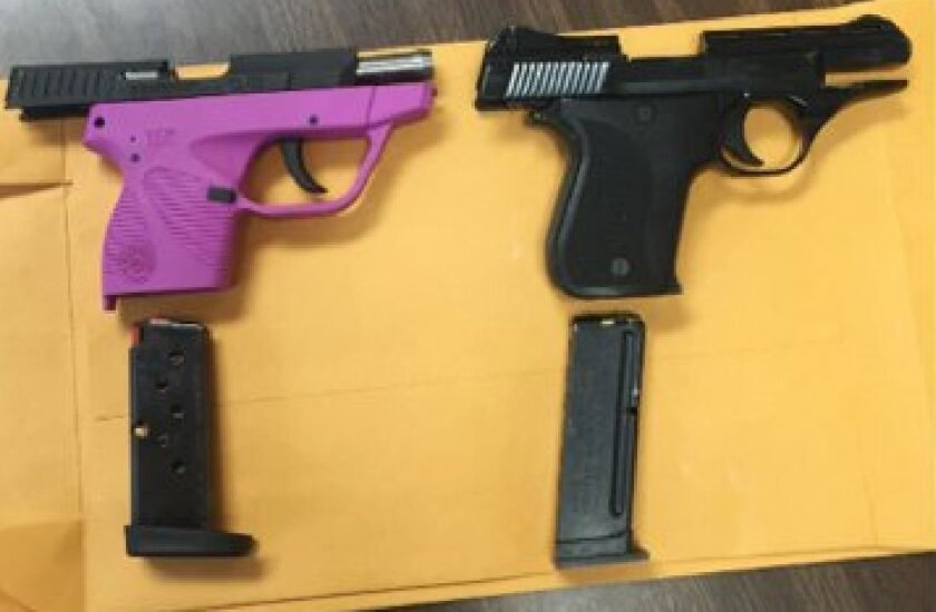 In this photo provided by Kentucky State Police, handguns sit on a table Thursday, April 30, 2015. A first-grader and his brother in kindergarten took two handguns, one of them loaded, on a bus to Dewitt Elementary School in Flat Lick, Ky., after apparently thinking they were toys, authorities said