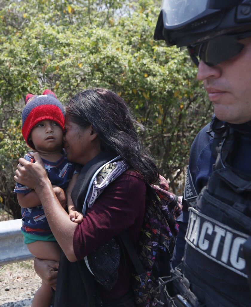 A Central American migrant woman and her son walk with a Mexican Federal Police agent as they are ta