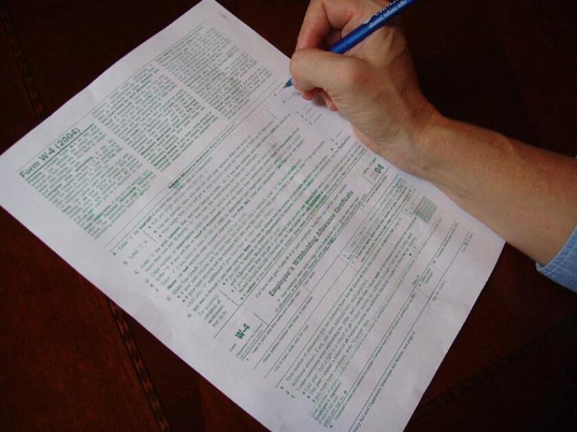 Vista de una persona que llena uno de los formularios para pagar impuestos. En el último día para pagar impuestos, las organizaciones proinmigrantes recuerdan que los indocumentados que residen y trabajan en el país pagan miles de millones de dólares en impuestos destinados a las arcas públicas federales, estatales y locales. EFE/Archivo
