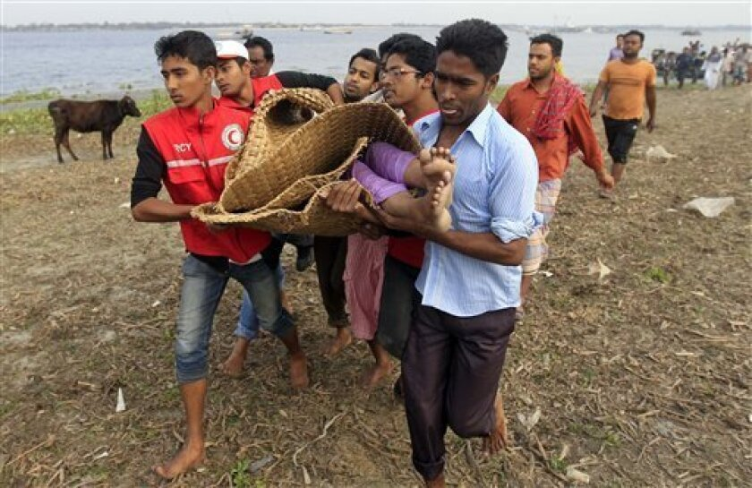 Rescue workers carry the body of a victim of a ferry that capsized in Meghna River at Munshiganj, 32 kilometers (20 miles) south of Dhaka, Bangladesh, Friday, Feb. 8, 2013. A passenger ferry capsized Friday after colliding with another ship on a river in central Bangladesh, dumping as many as 100 people into the water, officials and witnesses said. (AP Photo/A.M. Ahad)