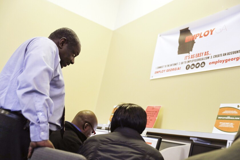 Georgia Department of Labor services specialist Eric Frasier, left, helps a woman with a job search at an unemployment office in Atlanta on March 3.